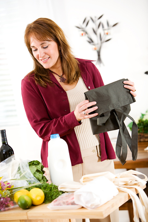 reusable: Reusable: Woman Finished Unpacking Groceries Stock Photo