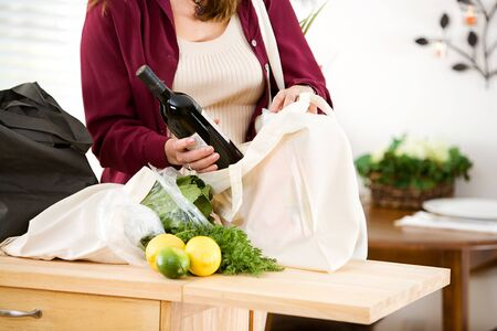 reusable: Reusable: Woman Removes Wine From Fabric Grocery Bag Stock Photo