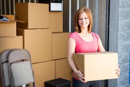 cajas de carton: Almacenamiento: La mujer con cajas detrás de la
