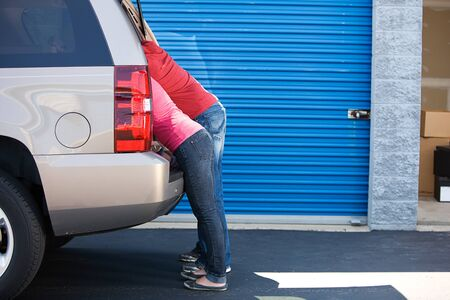 leaning on the truck: Storage: Man and Woman Leaning into SUV Stock Photo