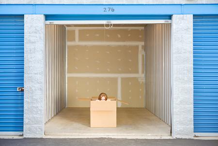 Opslag: Vrouw Gluren Om buiten kant van Box in Unit
