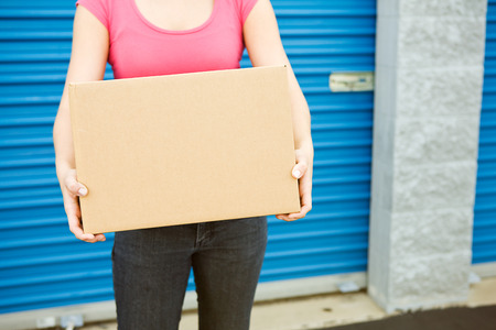 storage box: Storage: Woman With Box Stands By Door