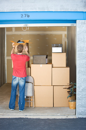 Storage: Man Adds to Storage Unit