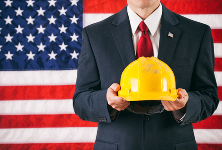 yellow hard hat: Politician: Man Holding Up Yellow Hard Hat