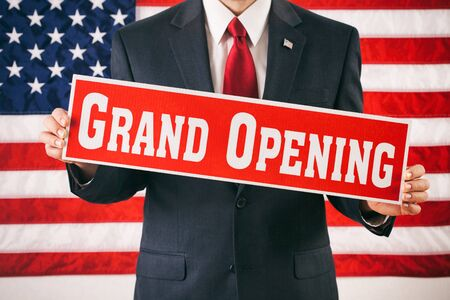 politician: Politician: Man Holding Up Grand Opening Sign