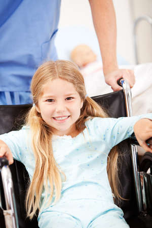 pushes: Hospital: Nurse Pushes Girl with Pigtails in Wheelchair
