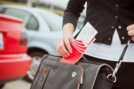 persona viajando: La mujer viaja con una maleta de mano y una bolsa de ordenador portátil.
