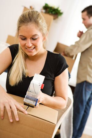 moving box: Moving: Cheerful Woman Tapes Packing Box Stock Photo