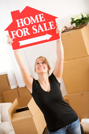 home sale: Moving: Woman Holds Up Home Sale Sign