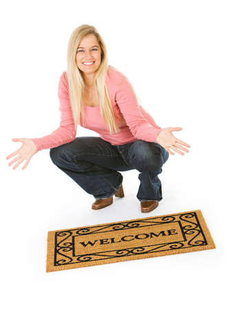 welcome mat: Moving: Woman Posing With Welcome Mat Stock Photo
