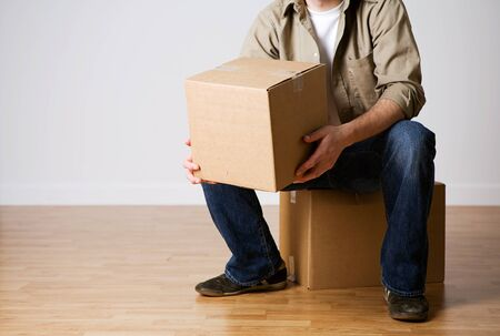 moving box: Moving: Man Sitting And Holding Cardboard Box