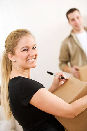moving box: Moving: Woman Writing With Pen on Shipping Box Stock Photo