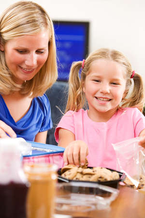 finishing touches: Student: Girl And Mother Put Finishing Touches On School Lunch