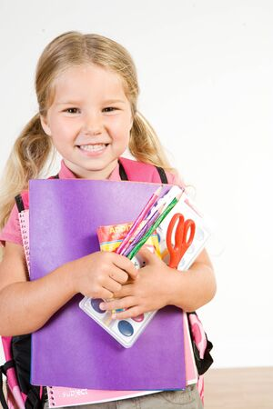 Education: Smiling Girl With Armful Of School Supplies Stock Photo