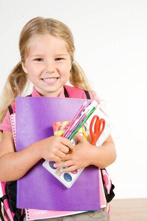 Onderwijs: glimlachend meisje met armful van schoolbenodigdheden