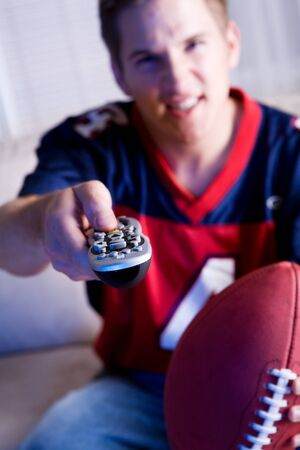 changing channels: Football: Guy Holds Remote Control And Watches Team On TV Stock Photo