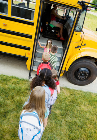School Bus: Kids Getting On Bus Stockfoto