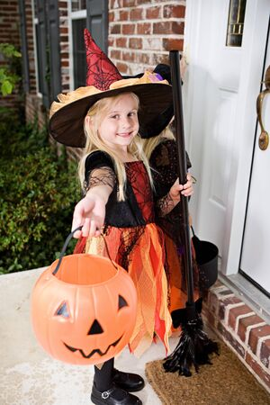Halloween: Girl Witches On Porch Ringing Doorbell Stock Photo