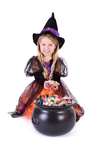 goodies: Halloween: Girl Witch Digs Into Pot Of Halloween Goodies