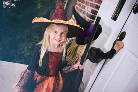 Halloween: Little Girl Waits For Door To Open On Front Porch Stock Photo - 61860726