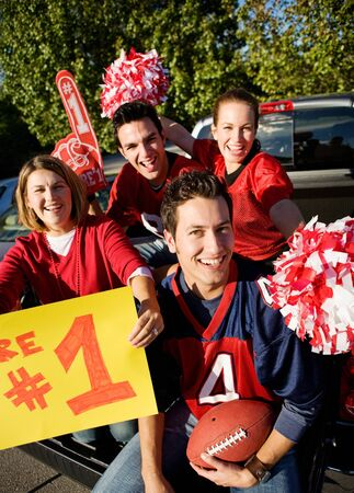 Tailgating: Excited Fans Cheering For Team And Holding Sign Stock Photo