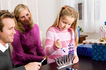 Hanukkah:  Girl Puts Candles in Menorah