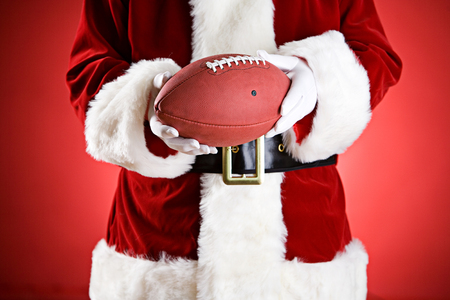 anonymous people: Santa: Holding An American Football