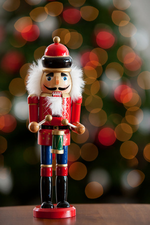 Christmas: Traditional Wooden Nutcracker With Tree Behind Stock Photo