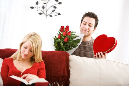 Valentines: Man Sneaks Up with Valentine Gifts For Girlfriend Stock Photo