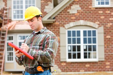 新しい家の建築現場でのシリーズ。 建設労働者ビルダー、不動産業者、若い白人のカップルが含まれています