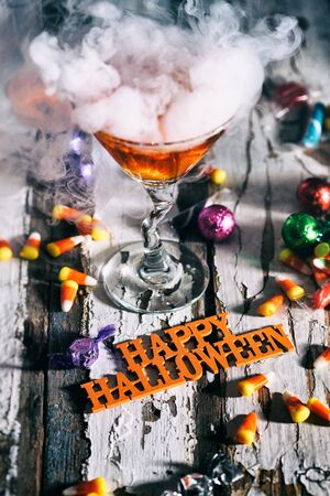 wispy: Halloween: Orange Potion In Martini Glass With Happy Halloween In Front Stock Photo