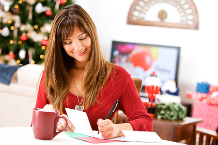 Christmas: Writing Holiday Cards at Table Stock Photo