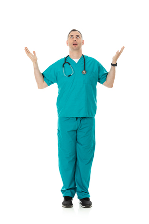 Humorous male doctor in scrubs in a variety of poses on a white isolated background. Unsure and confused male with hands raised. 写真素材