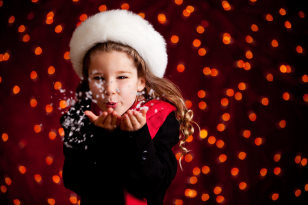 Beautiful holiday series with a cute girl on a glowing red background, dress in winter clothing.  Suitable for Christmas use, with lots of copyspace.