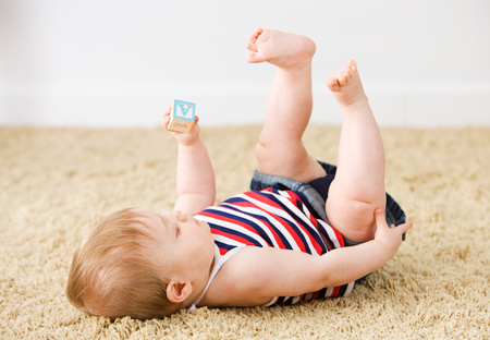 Cute Caucasian baby, on carpet, indoors, with various props. Stock Photo