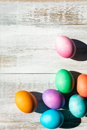 A rainbow of Easter Eggs on a white and weathered wood background.