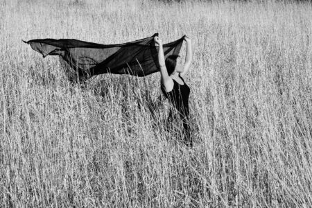 Lady in black dress walking through field