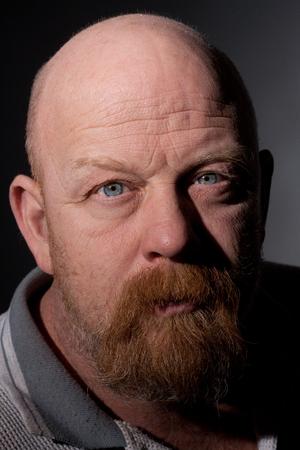 grown ups: Harsh light portrait of a balding man with facial hair.