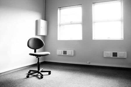 typist: Black and white image of a single office typist chair in an empty office