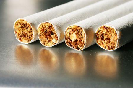 unfiltered: four cigarettes on a cigarette case Stock Photo