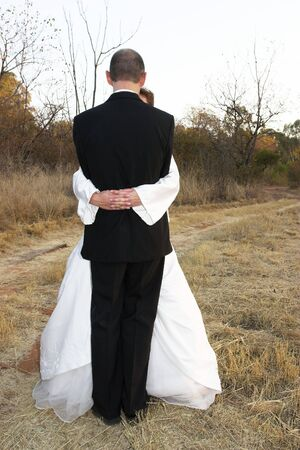 bridal couple: Bridal couple standing on a dirt road in an embrace Stock Photo