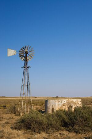 lack of water: Windpump and cement dam just outside Colesberg, south Africa