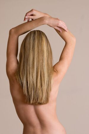 Naked blonde woman from behind - arms lifted