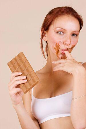 licking finger: Redheaded girl eating chocolate, licking finger Stock Photo
