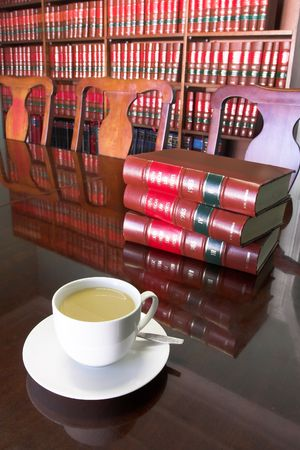 White Coffee cup with Legal Library in background and books on the table Stock Photo
