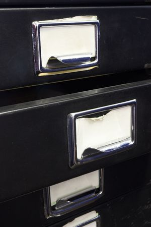 Close-up of a black mini filing cabinet and label with one open drawer photo