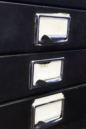 Close-up of a black mini filing cabinet and label with three closed drawers photo