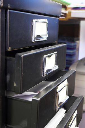 Close-up of a black mini filing cabinet and label with four open drawers photo