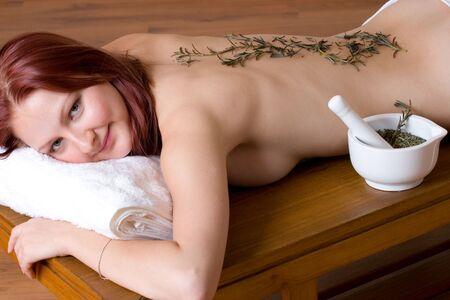 Woman lying on massage table with lavender twigs on clean naked back - Eyes open