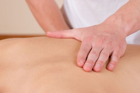 Woman lying on massage table with the hands of male masseuse on her back